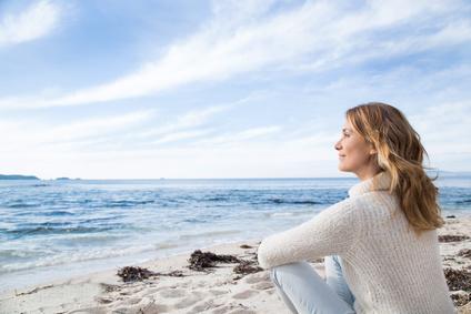 femme en hiver assise au bord de la mer